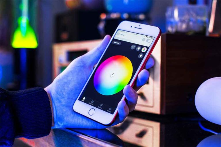 Sample app running on an iPhone. User is setting the lights to white. Background is illuminated blue and contains a yellow lava lamp