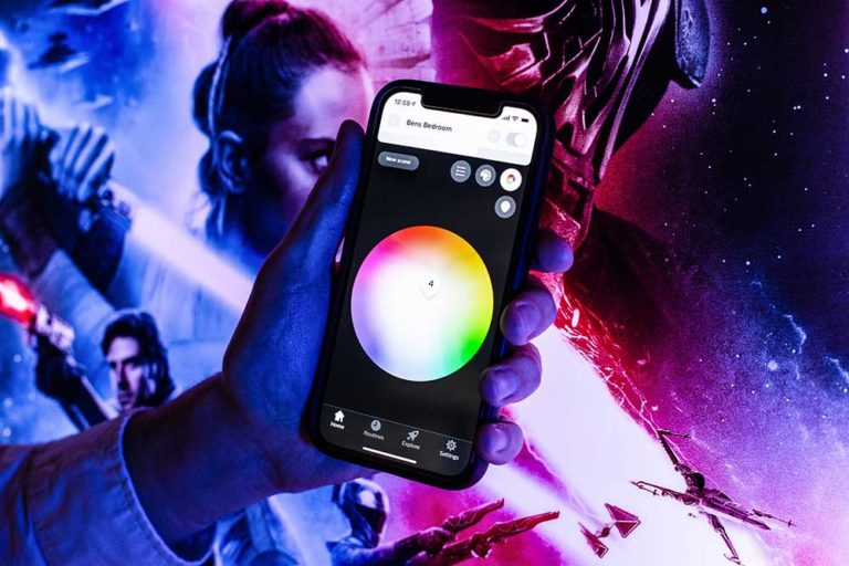 Philips Hue app running on iPhone 12. Phone is held with left hand against a Star Wars Illuminapp.