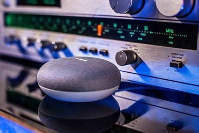 Google Home Mini in front of silver radio
